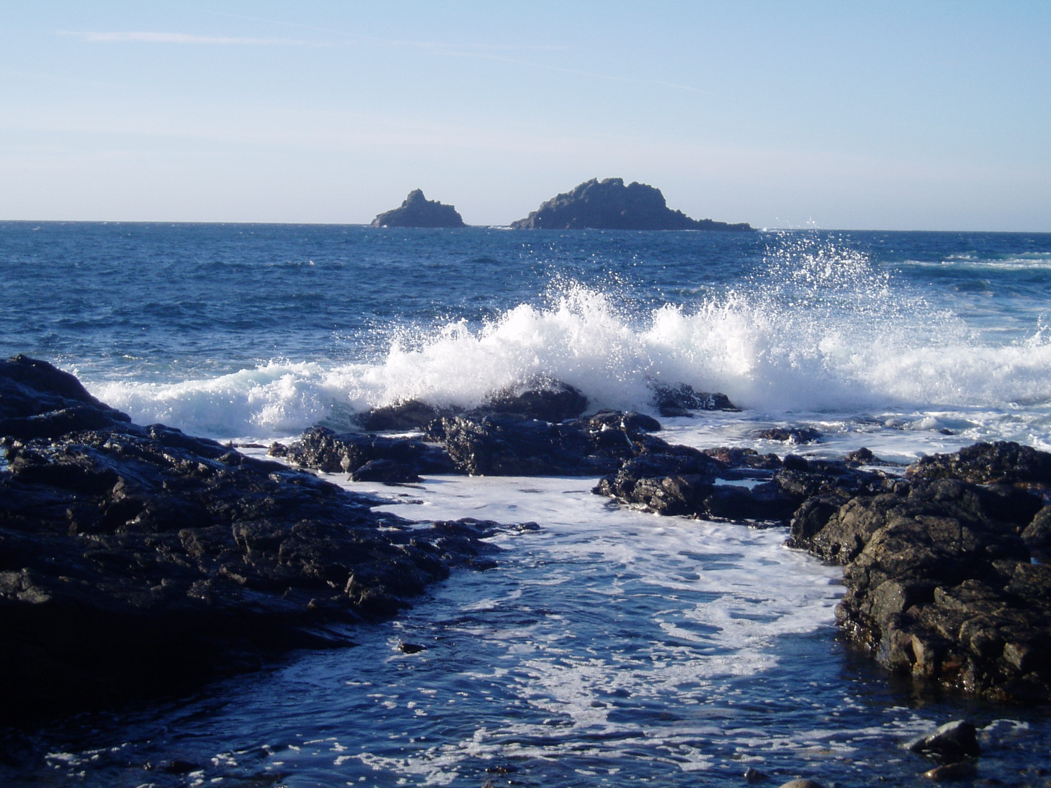 Waves breaking at Priests Cove, Cape Cornwall with The Brisons in distance